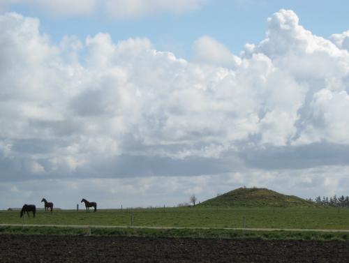 Hügelgrab mit Pferden, die in der Nähe weiden
