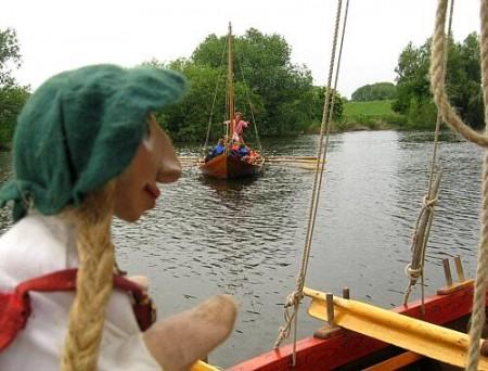 Embla blickt auf das Wasser, dort kommt ein Wikingerschiff angerudert.
