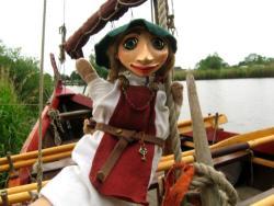 Wikingerhandpuppe an Bord eines Wikingerschiffes, im Hiuntergrund der Bug