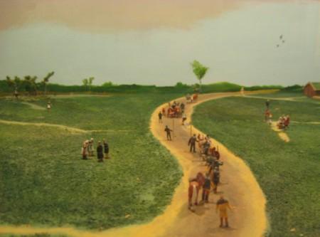 Miniaturmodell eines unbefestigten Weges, auf den Menschen mit einigen Tiere durch die flache Landschaft reisen