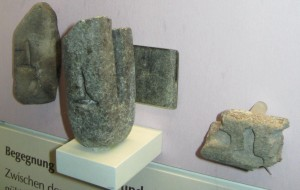 Gussform aus Stein, in der sich auf der Vorderseite eine Hohlform für einen Hammer und auf der Rückseite, über einen Spiegel sichtbar, eine kreuzförmige Hohlform befindet.